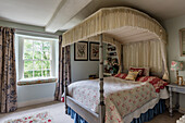 Antique four-poster bed in the English-style bedroom