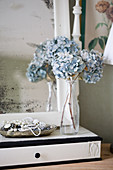 Dried blue hydrangeas in a vase on an old mirror