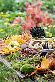 Table with moss, autumn leaves, chestnuts, berries, ornamental pumpkin, straw wreaths, and wreath tying tools