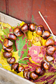 Autumn wreath made of chestnuts on colourful autumn leaves