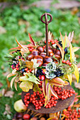 Chestnuts in a colourful autumn wreath of autumn leaves and berries