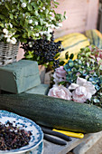 Ingredients for autumn decoration: courgettes, privet berries, roses, hydrangea blossoms, snowberry and damp sponge