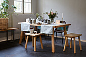 Gedeckter Tisch im Skandinavischen Stil mit Stühlen und Hockern