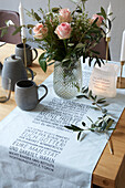 Bouquet of roses on set table, table runner with writing motif