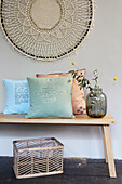 Cushions printed with writing on a wooden bench under macramé