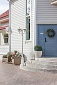 Traditionelles, weißes Holzhaus mit blauer Eingangstür