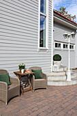 Rattansessel mit Tisch vor weißem Holzhaus