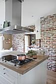 Abzugshaube über Kochinsel in der Küche mit Backsteinwand