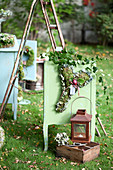 Herbst-Arrangement mit Herz aus Moos, Hortensienblüten und Zwiebel, Laterne und Holzkiste