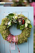 Door wreath of moss with ivy, hydrangea blossoms and Brussels sprouts