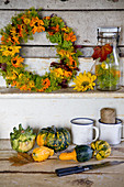 Autumn wreath of marigold blossoms and fennel, with ornamental pumpkins