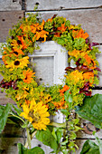 Bottle with umbel umbels and marigold blossoms, behind it an autumn wreath