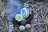 Easter basket with hand-painted Easter egg, filled with primrose flowers and feathers, branches of Cherry plum blossoms, and Easter eggs