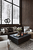 Coffee table in the living room in natural colours with view of snowy landscape