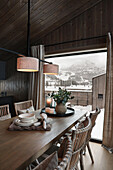 Dining table with dishes in open kitchen, view of snowy landscape