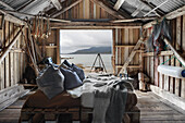 Pallet bed with pillows in rustic wooden shed
