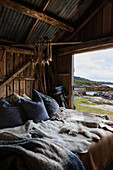 Pallet bed with cushions and animal fur in rustic wooden shed