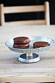 A homemade cake stand made from zinc plates and a wooden stick