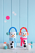 Whimsical snowman decorations made from toilet roll cores, pipe cleaners and pompoms