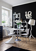 Designer chairs at round dining table in front of black wall