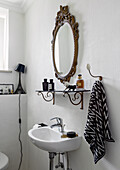 Antique mirror and shelf in the white bathroom with textured wallpaper