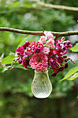 Small bouquet with zinnia, carnation, snapdragons, and florets in a hanging glass vase