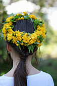 Woman wearing wreath of double Japanese marigold bush flowers on head