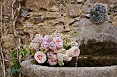 Fragrant spring bouquet of lilacs and roses in basin of wall fountain