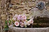 Duftender Frühlingssstrauß aus Flieder und Rosen am Wandbrunnen