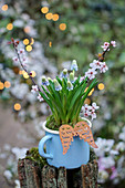 Grape hyacinths in pale blue enamel mug decorated with cherry plum blossom and angel wings