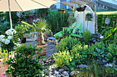 Small garden with lady's mantle, hemp palm in terracotta tubs and loungers