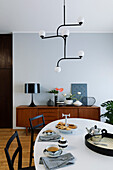Oval dining table in front of retro sideboard