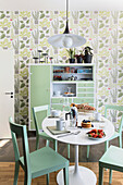 White table with green chairs and vintage sideboard