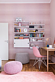 Desk and shelf in the girls' room with pink wallpaper