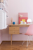 Desk with classic chair and shelf in the girls' room with pink wallpaper