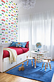 White bed, children's table with chairs in the boys' room, wallpaper with a car motif