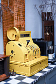 Old, yellow, metal cash register used as vintage decoration