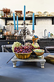 Vintage arrangement of grapes, bust and candelabra on kitchen table