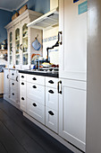 Weiße Landhausküche mit Farbakzenten in Weiß und Blau