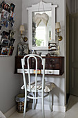 Chair at wall-mounted dressing table and family photos in postcard rack