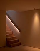 Modern staircase with indirect lighting behind handrail