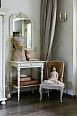 Puppe auf altem Barockstuhl und Modepuppe auf Konsolentisch