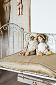 Teddy bear and doll on old metal bed with hessian-covered mattress