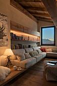 Gemütliche Sofagarnitur, darüber Holzregale im Wohnzimmer mit Dielenboden und Holzdecke