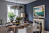 Gedeckter runder Esstisch mit Hussenstühlen im Esszimmer mit blauer Wand