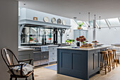 Kücheninsel mit Barhockern vor Küchenzeile