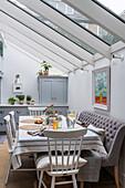 Esstisch mit Stühlen und Polsterbank unter Glasdach