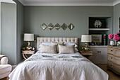 Doppelbett, flankiert von zwei Nachttischen mit Lampen im Schlafzimmer mit grauen Wänden