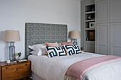 Doppelbett mit hohem Kopfteil, daneben Nachttisch mit Lampe
