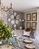 Gedeckter runder Tisch unter französischem Kronleuchter, Teller und botanische Drucke an den Wänden